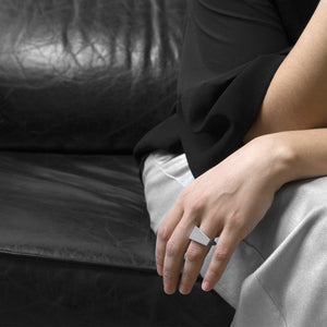 A person wearing the Aluminium Square Ring on their ring finger while sitting on a black leather sofa