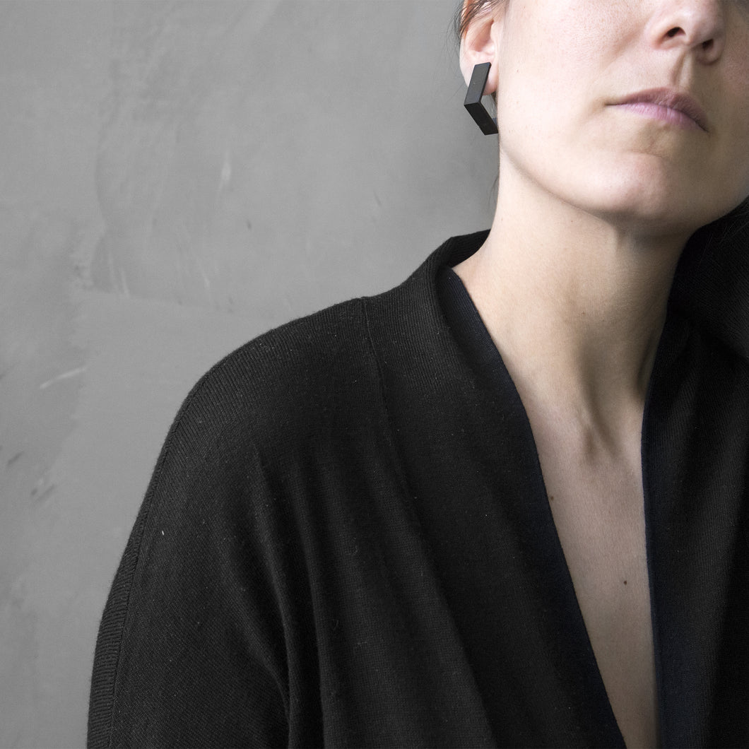 A woman wearing the Black Square Earrings with a black bluse on a grey background
