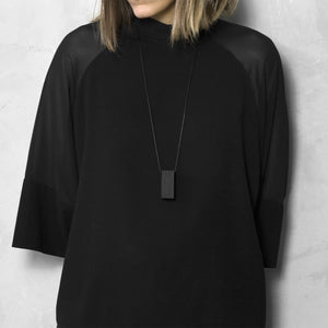 A woman with a blond hair wearing the Black Rectangle Necklace with a black bluse on a grey background