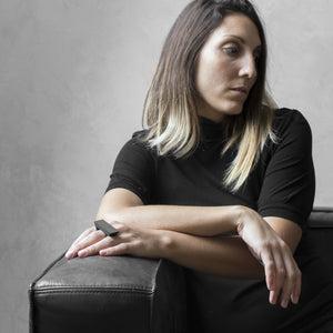 A woman wearing the Asteroid Ring on their ring finger while sitting on a black leather sofa with a concrete grey background