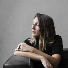 Load image into Gallery viewer, A woman wearing the Asteroid Ring on their ring finger while sitting on a black leather sofa with a concrete grey background