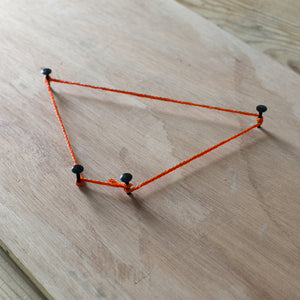The Asteroid project, with four nails and an orange string on on a wooden board