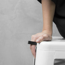 Load image into Gallery viewer, A woman wearing the Megalith Ring on their ring finger while sitting on a white chair with a concrete grey background