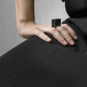 A woman wearing the Megalith Ring on their ring finger while sitting on a black on a concrete grey background