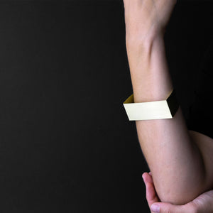 woman arm that are wearing MOON bracelet in brass with black background