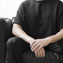 Load image into Gallery viewer, A man wearing the Black MODULOUNO Necklace with a black t-shirt on a grey background while sitting on a black sofa