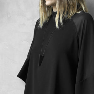 A woman with a blond hair wearing the Black MODULOCINQUE Necklace with a black bluse on a grey background