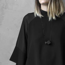 Load image into Gallery viewer, A woman with a blond hair wearing the Black MODULODUE Necklace with a black bluse on a grey background