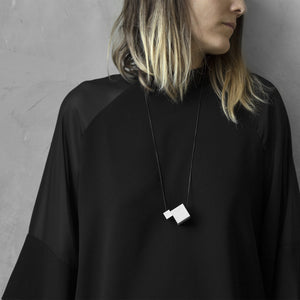 A woman with a blond hair wearing the Grey MODULODUE Necklace with a black bluse on a grey background