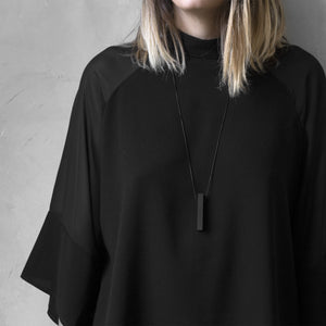 A woman with a blond hair wearing the Black MODULOQUATTRO Necklace with a black bluse on a grey background