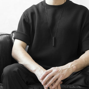 A man wearing the Black MODULOQUATTRO Necklace with a black t-shirt on a grey background while sitting on a black sofa