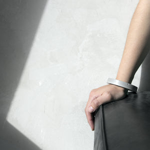 A person wearing the Grey Colosseum Bangle with a grey background