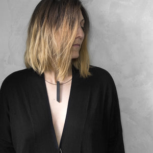 A woman with a blond hair wearing the Black Column Necklace with a black bluse on a grey background