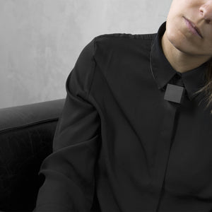 A woman with a blond hair wearing the White Cube Necklace with a black bluse on a grey background
