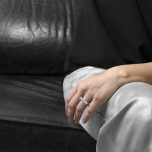 Load image into Gallery viewer, A person wearing the Aluminium Square Ring on their ring finger while sitting on a black leather sofa