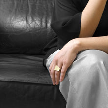 Load image into Gallery viewer, A person wearing the Brass Square Ring on their ring finger while sitting on a black leather sofa