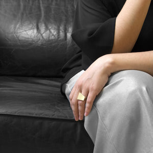 A person wearing the Brass Square Ring on their ring finger while sitting on a black leather sofa