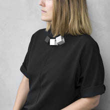 Load image into Gallery viewer, A woman with a blond hair wearing the Zero Elements Necklace with a black bluse on a grey background