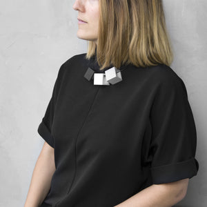A woman with a blond hair wearing the Zero Elements Necklace with a black bluse on a grey background