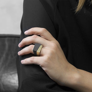 A woman wearing the Assembled Ring, a combination of MK3 black asymmetric ring and Brass squared ring, on their ring finger while sitting on a black leather sofa