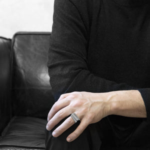 A man wearing the Assembled ring on their ring finger, a combination of 3 Aluminium square rings, while he sitting on a black leather sofa