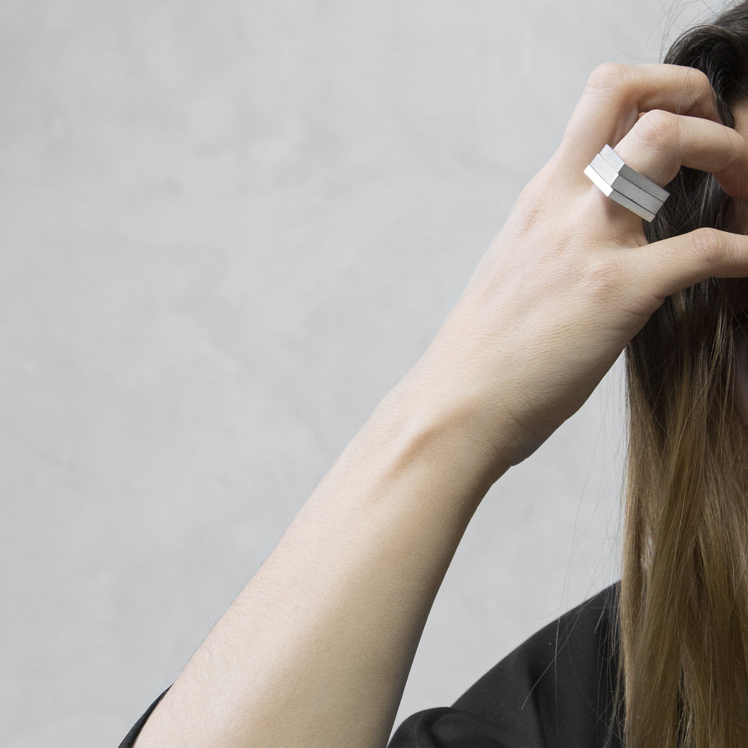 A woman wearing the Assembled ring on their ring finger, a combination of 3 Aluminium square rings
