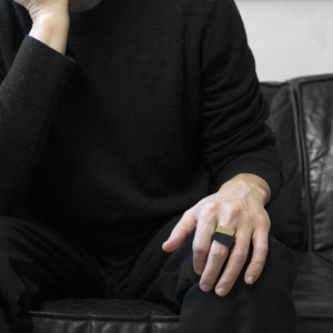 A man wearing the Assembled Ring, a combination of MK3 black asymmetric ring and Brass squared ring, on their ring finger while sitting on a black leather sofa