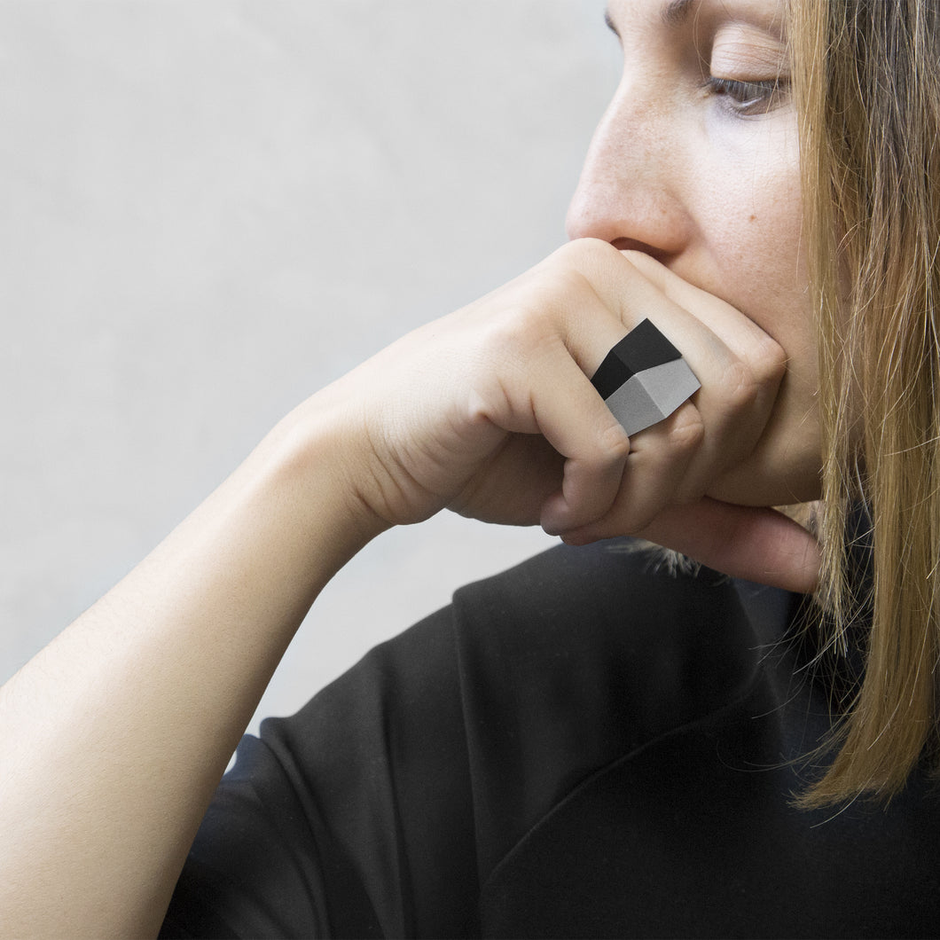 A woman wearing the Assembled Ring, a combination of MK3 black asymmetric ring and MK3 Grey asymmetric ring, on their ring finger