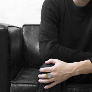 man wearing the Assembled ring, a combination of Aluminium square ring and brass square ring, seat on black sofa