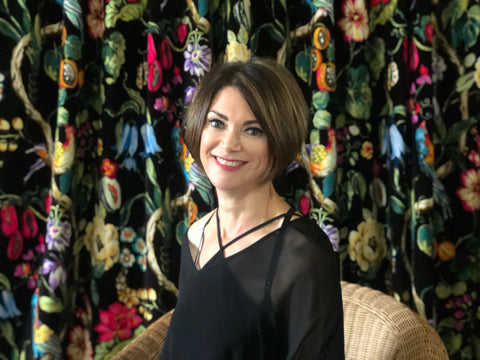 BRONWYN SHEEHAN CHRISTCHURCH SITTING IN FRONT OF FLORAL DRAPES