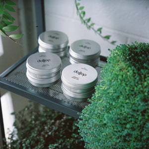 dollop pomade stacked on shelf surrounded by green pot plants