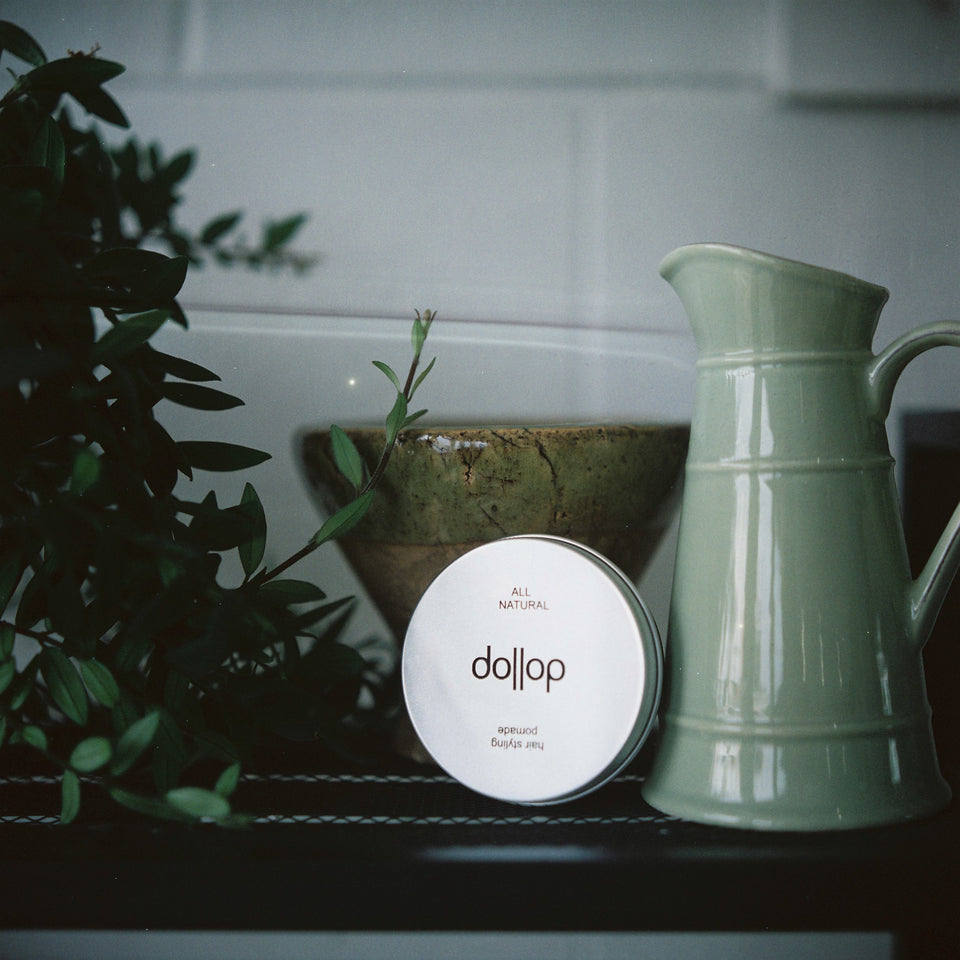 Shelf with tin of dollop pomade surrounded by lush plants and green pottery bowl and jug