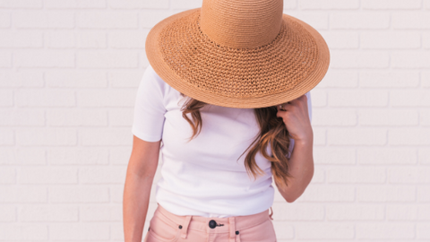woman in a sunhat protecting face from sun