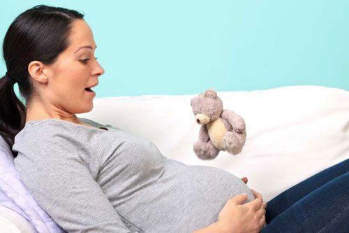 7-things-you-need-to-know-about-the-second-trimester-mom-feeling-baby-kick-on-couch