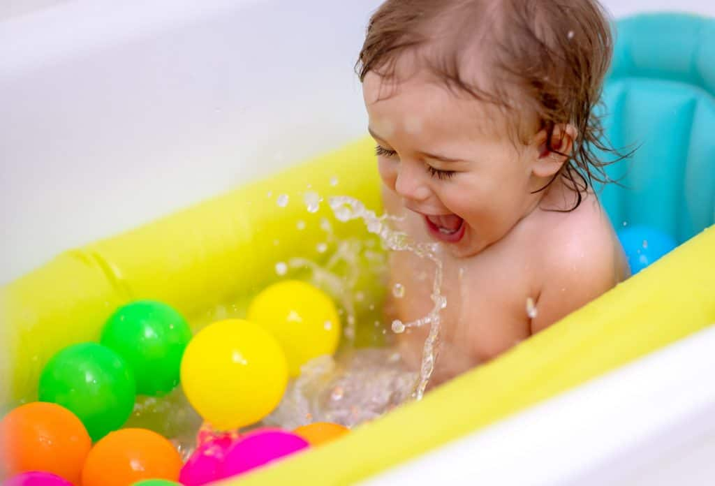 A toddler sitting in the tub