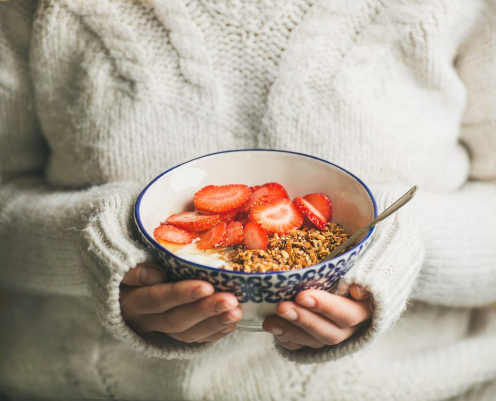 Healthy breakfast yogurt, granola, strawberry bowl in hands of woman
