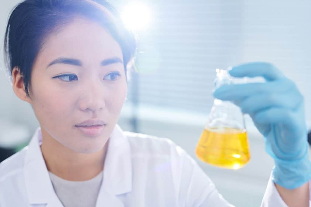 Laboratory worker examining chemical liquid