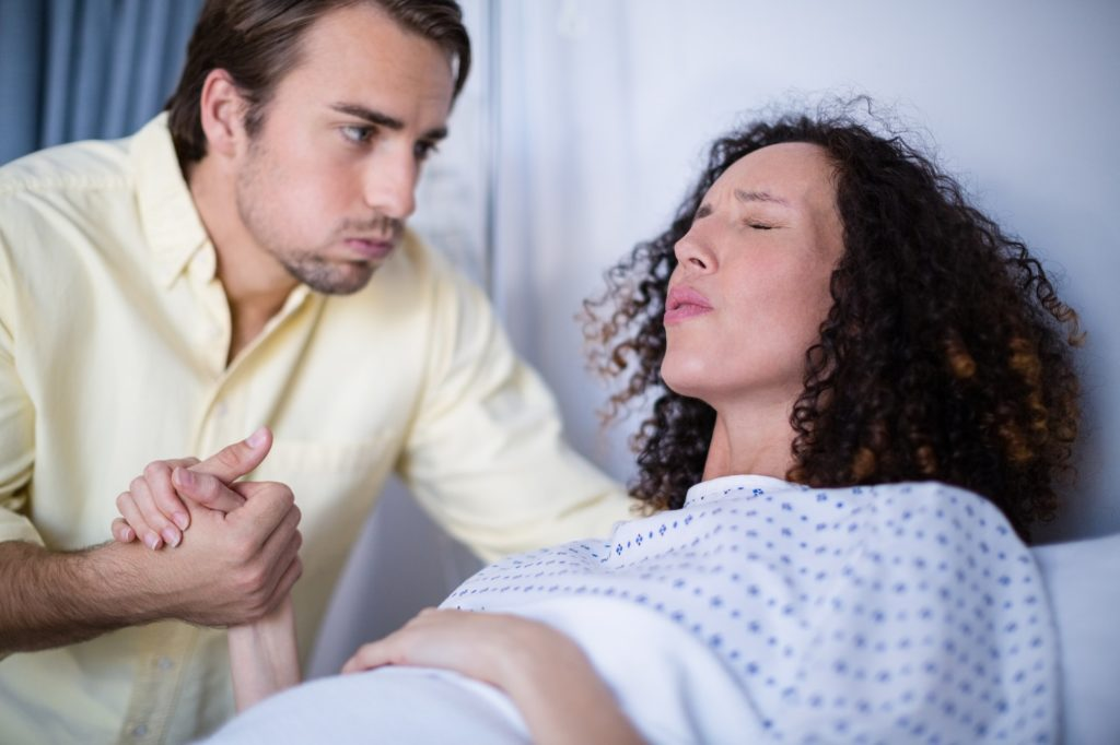 Man comforting pregnant woman during labor in ward