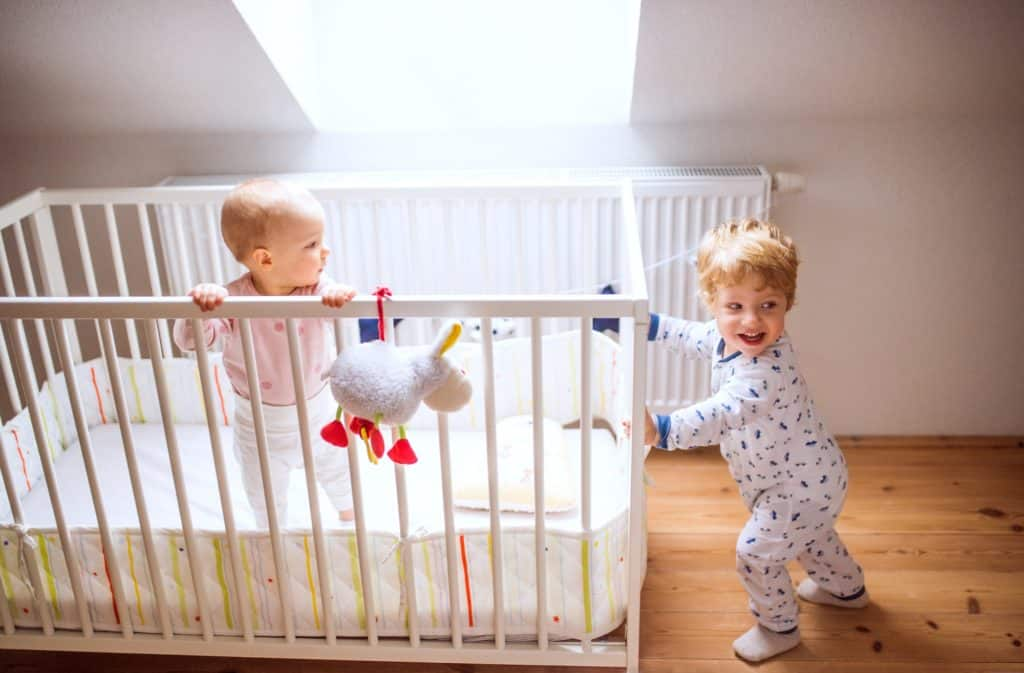 Two toddler children playing in a crib at home