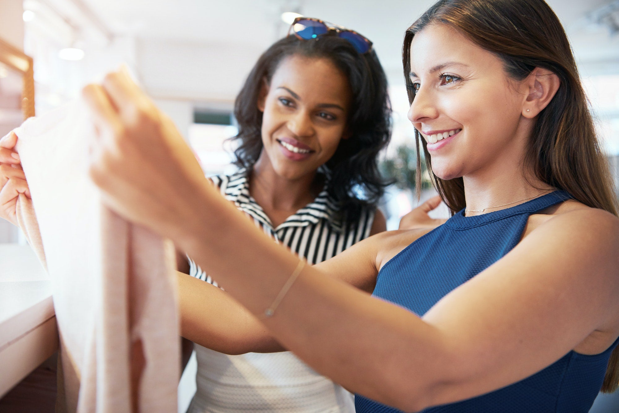 Two young female friends shopping for clothes
