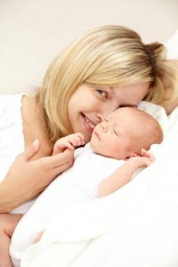 what-to-expect-when-your-baby-is-born-mom-snuggling-with-sleeping-baby