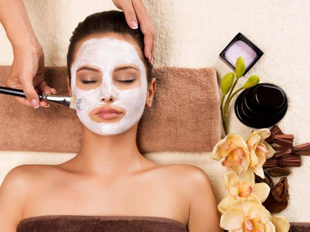 Woman having a facial cosmetic mask at spa salon.