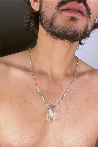 A lingam shaped hanging crystal quartz pendant on a silver neck chain.