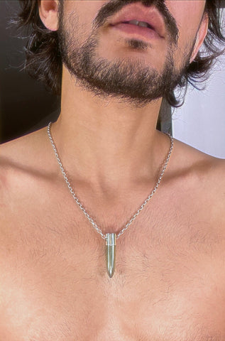 A lingam shaped hanging pyrite crystal pendant on a silver neck chain.