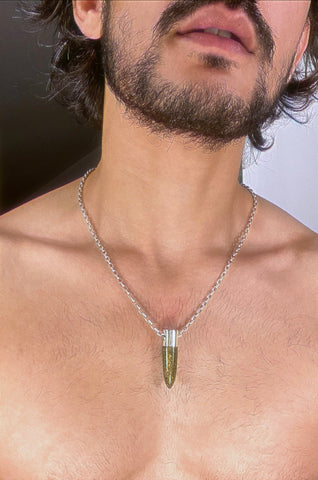 A lingam shaped hanging Bronzite crystal pendant on a silver neck chain.
