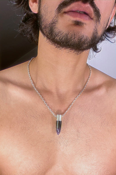 A lingam shaped hanging Amethyst crystal pendant on a silver neck chain.