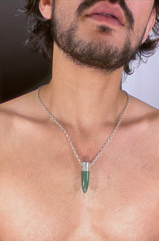 A lingam shaped hanging Aventurine crystal pendant on a silver neck chain.