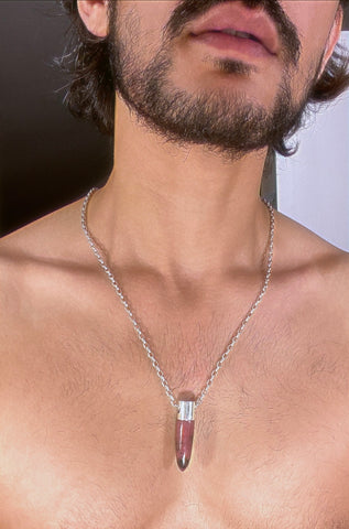 A lingam shaped hanging Rhodonite crystal pendant on a silver neck chain.