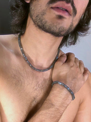 A portrait of an indian boy wearing a labradorite necklace and bracelet.