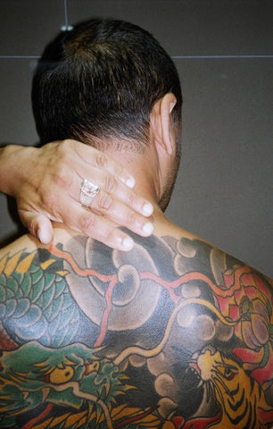 a koi star spinner ring on an indian boy with a back full of colorful tattoos.